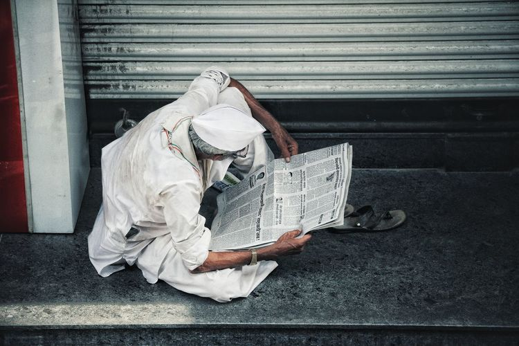 High angle view of man reading book on footpath