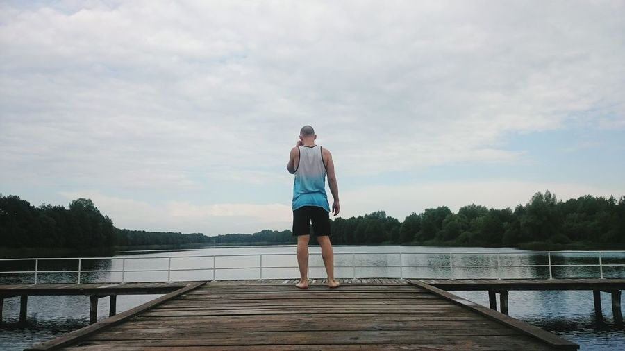 Rear View Of Man On Pier On Lake