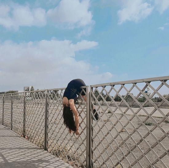 Full length of woman on fence against sky