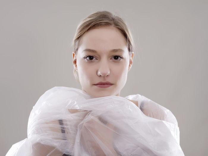 Portrait of young woman in plastic against gray background