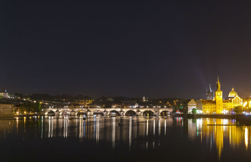 View of the famous Charles Bridge illuminated at night. Charles Bridge is a historic gothic-style stone bridge that crosses the Vltava river in Prague connecting the Old Town to the Lesser Quarter. Dark sky for copyspace Bohemia Charles Czech Dark Gothic Lights Prague Vltava Bridge Bulb City Historical Illuminated Lesser Night Old Pillar Quarter  Reflection Republic River Stone Town Urban Water