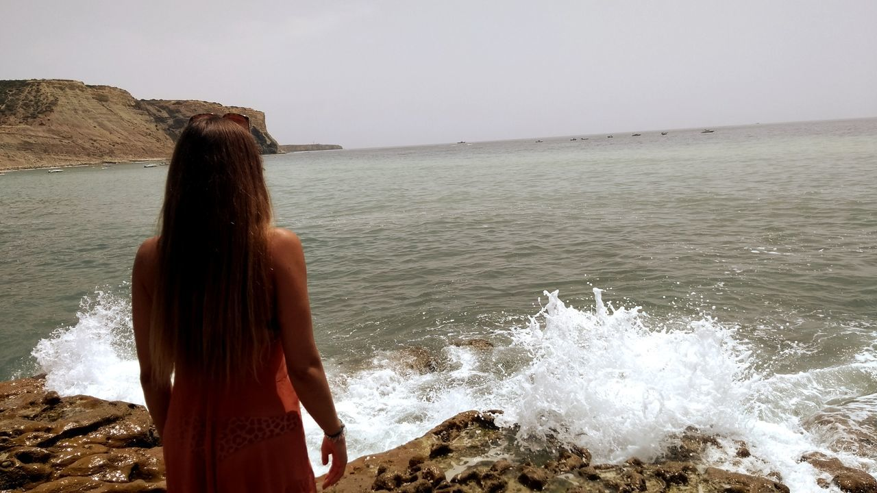 sea, real people, rear view, water, one person, standing, rock - object, wave, nature, horizon over water, beach, beauty in nature, lifestyles, day, scenics, leisure activity, outdoors, women, motion, clear sky, sky, ankle deep in water, young adult