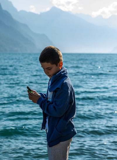 Side view of boy holding mobile phone against sea