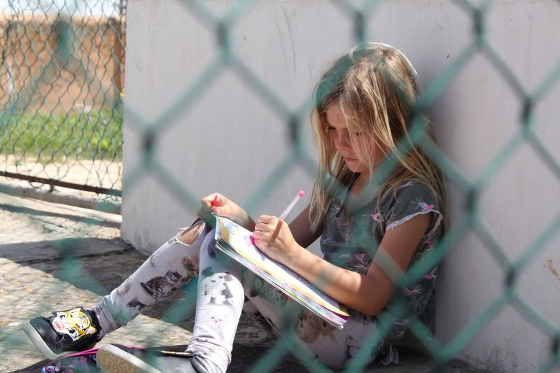 Girl With Book Seen Through Chainlink Fence