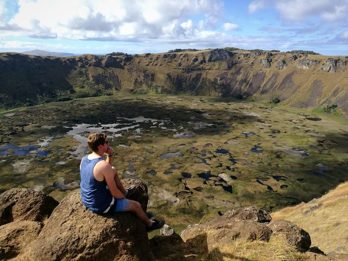 High Angle View Of Hiker Looking At View While Sitting At Crater Lake Of Rano Kau