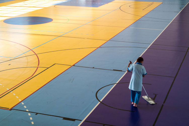 Rear view of woman cleaning basketball court