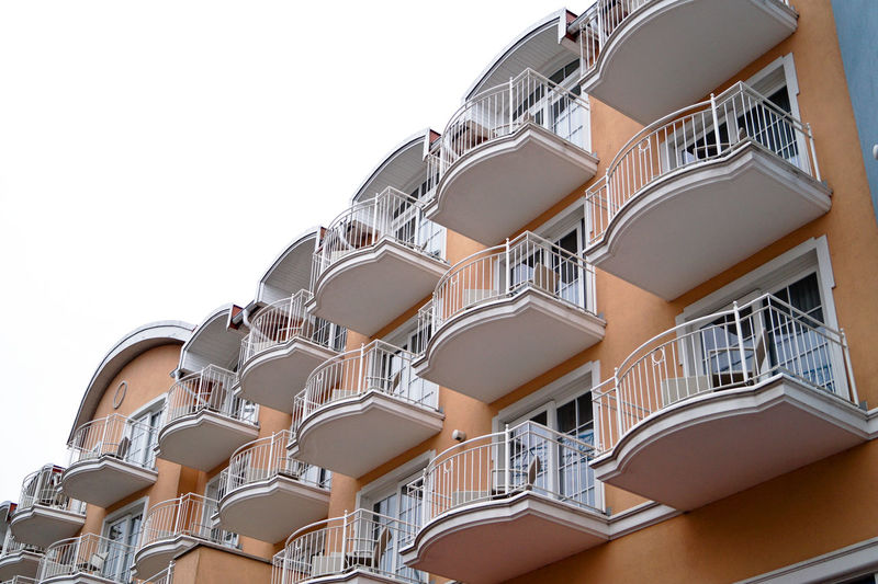Low angle view of white balconies on building against clear sky