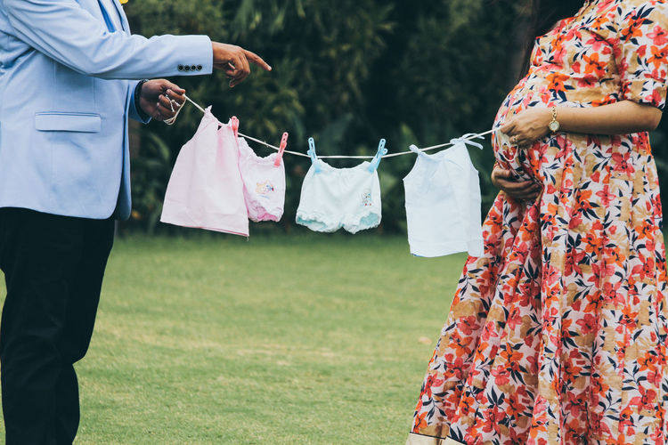 Midsection of pregnant woman with man holding baby clothing on field