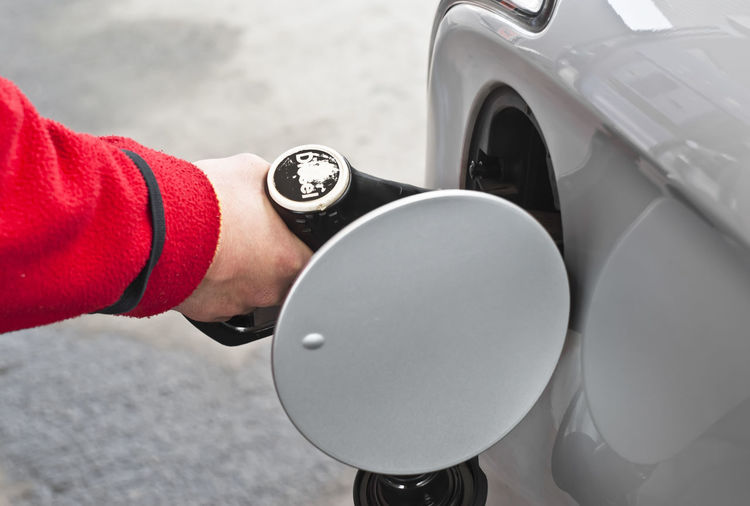 Cropped hand of person fueling car at gas station