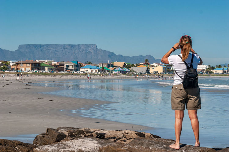 Rear view of woman with backpack looking at houses while standing on shore against clear blue sky
