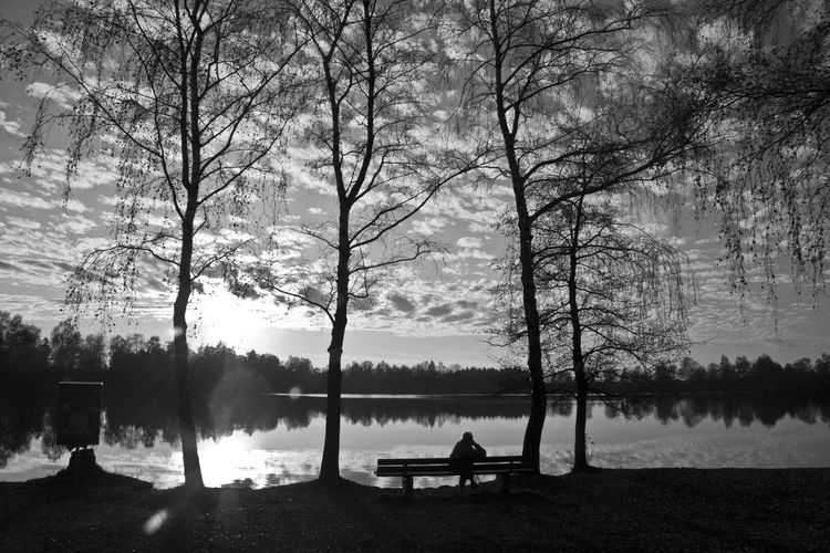 Silhouette Man Sitting On Bench At Lakeshore Against Sky