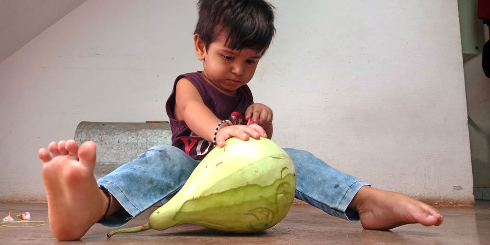 Full length of boy holding food while sitting on floor