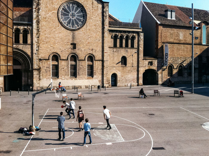 High angle view of boys playing at basketball court during sunny day