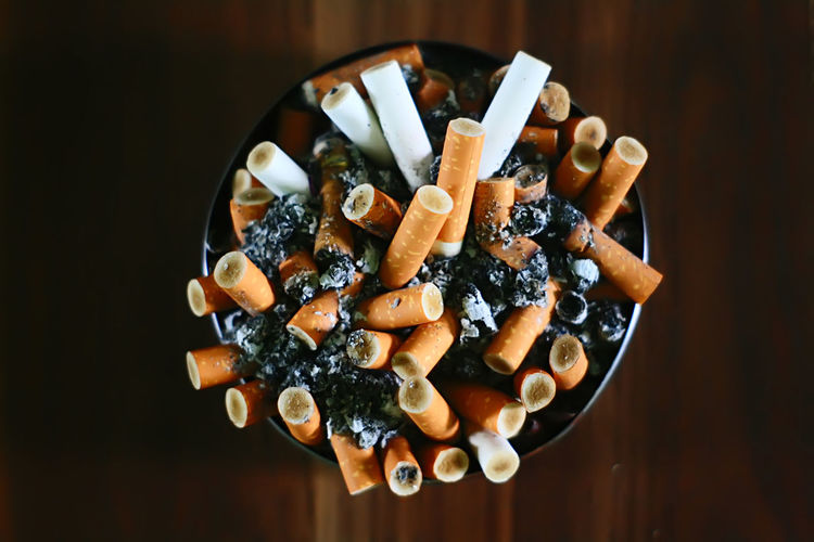 Close-Up Of Cigarette Butts In Ashtray On Table