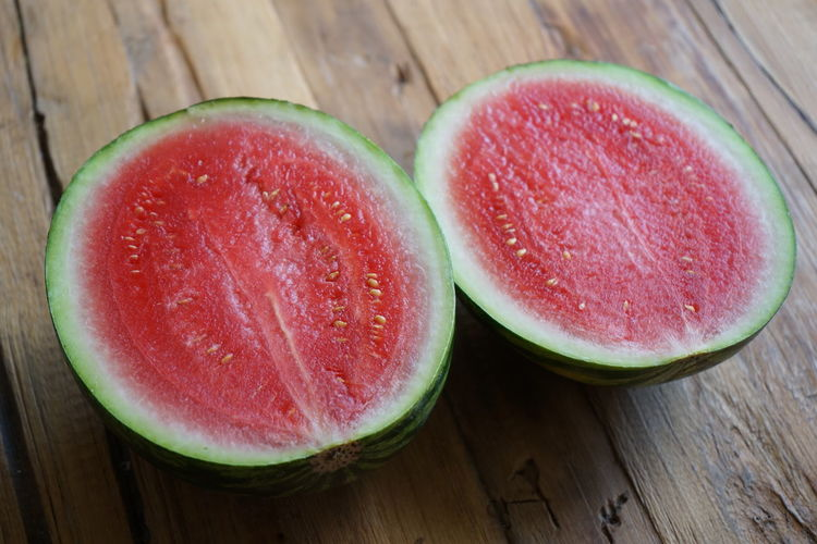 Sliced Watermelon on wooden table Green Green Color Close-up Cross Section Food Food And Drink Freshness Fruit Green Color Healthy Eating High Angle View Indoors  Juicy No People Pink Color Red Ripe SLICE Still Life Table Watermelon Wellbeing Wood - Material