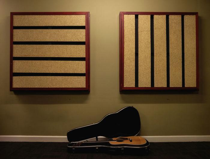 Acoustic guitar on floor against wall