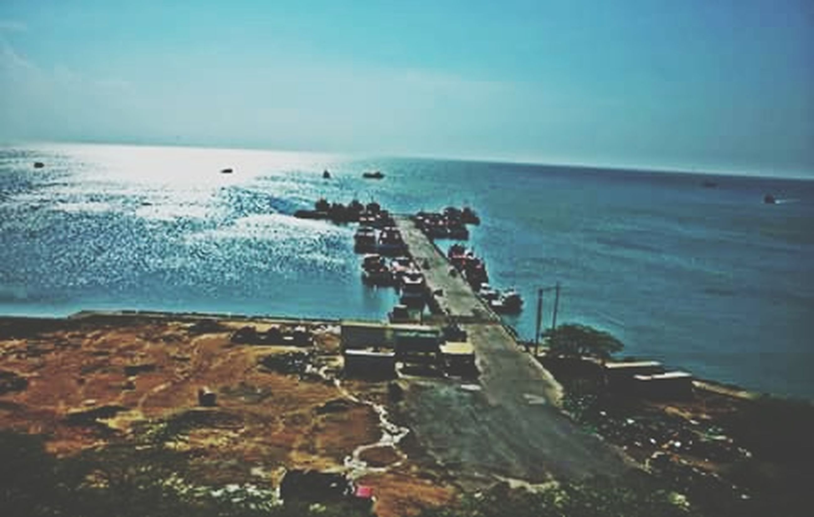 sea, horizon over water, water, beach, sky, shore, nautical vessel, nature, mode of transport, scenics, transportation, tranquility, beauty in nature, tranquil scene, high angle view, incidental people, outdoors, day, boat, rock - object