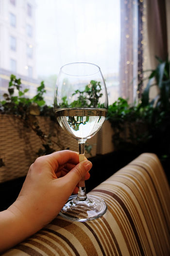 Close-up of hand holding glass of wine in dark atmospheric bar