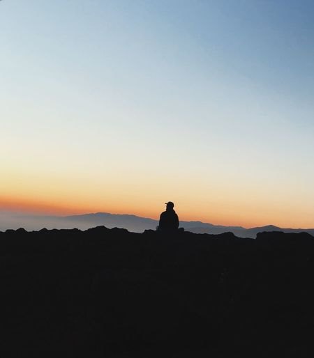 Silhouette man sitting on rock against orange sky
