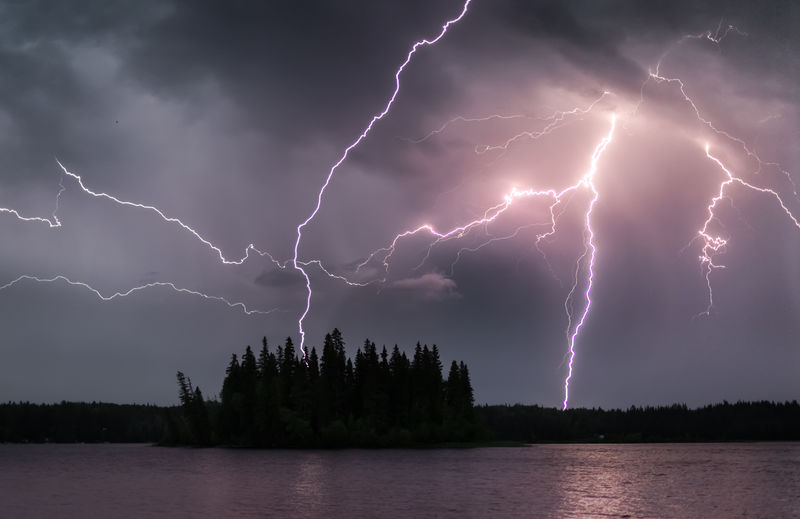 I finally got a chance to edit up another shot from the severe lightning storm over Prince George a few weeks ago. In contrast to the other lightning shot at sunset this one is from just after dusk. In the high resolution version of this you can clearly see the purple fringing on the edge of the lightning bolts. The lightning itself emits pure white light however the discharge though the atmosphere actually creates a plasma and the purple colour comes from this ionisation of the atmospheric gases. Ionisation is the same phenomena that causes the colour we see in polar Auroras. Plasma is neither solid, liquid, nor gas, rather it is a fourth state of matter. It is quite rare on earth however over 99% of the matter in the universe exists as plasma, held within stars or as superhot interstellar matter. We had a beautiful display of the storm looking back towards it out at Ness Lake as the cell passed mostly to the east of us and we avoided the flooding rain they received in town. Storms like this are rare up here in Northern BC and we lost power for a couple of hours. I must say it made me a little homesick for the frequent severe lightning storms we used to watch from our property in the mid latitudes of Australia. Love Life, Love Photography Lightning Strikes Beauty In Nature Bolts Canada Cloud - Sky Forked Lightning Island Lake Lake View Lightning Lightning Storm Nature Night No People Northern British Columbia Outdoors Power Power In Nature Purple Sky Storm Storm Cloud Thunderstorm Water Waterfront