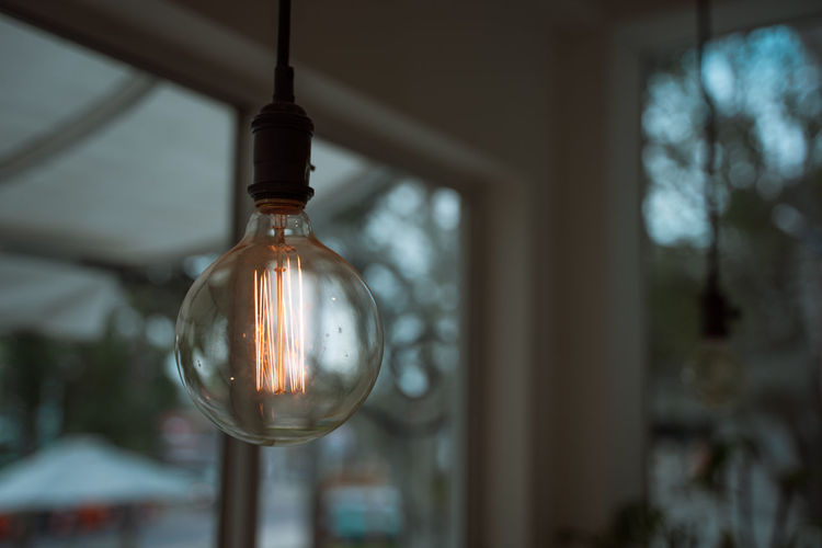 Low angle view of illuminated light bulb at home
