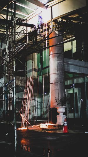 Low angle view of illuminated construction site at night