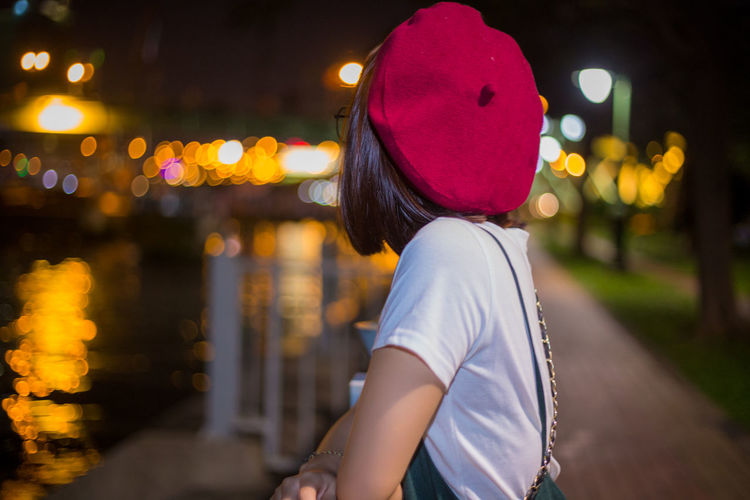 Side view of young woman standing at railing against canal in illuminated city during night