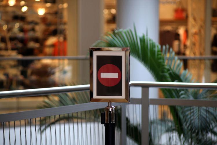 Close-up of warning sign on railing