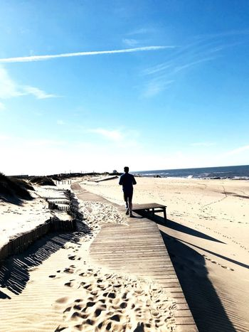Holzsteg Laufweg Strand Meer Jogging Full Length Beach One Person Day Sky Sand Sunlight Real People Tranquil Scene Men Outdoors Beauty In Nature Water Sea Shadow Tranquility Walking Scenics Standing Nature