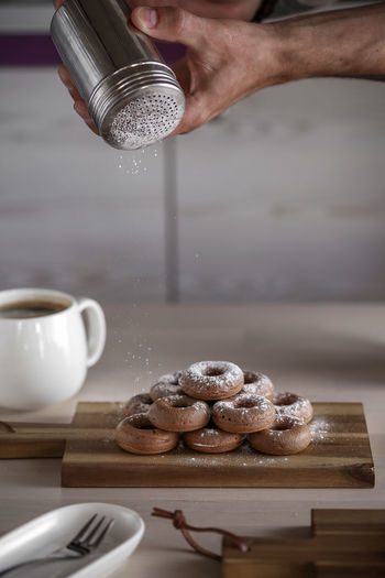Cropped Image Of Man Dusting Powdered Sugar On Donuts In Kitchen