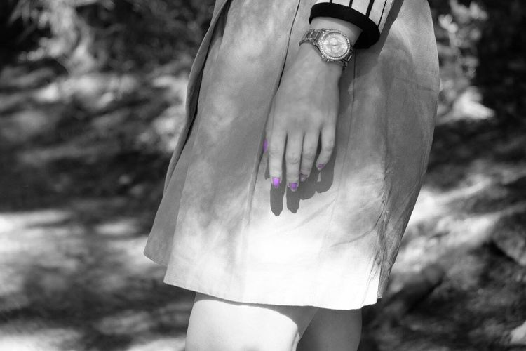 Midsection Of Woman With Purple Nail Polish In Park