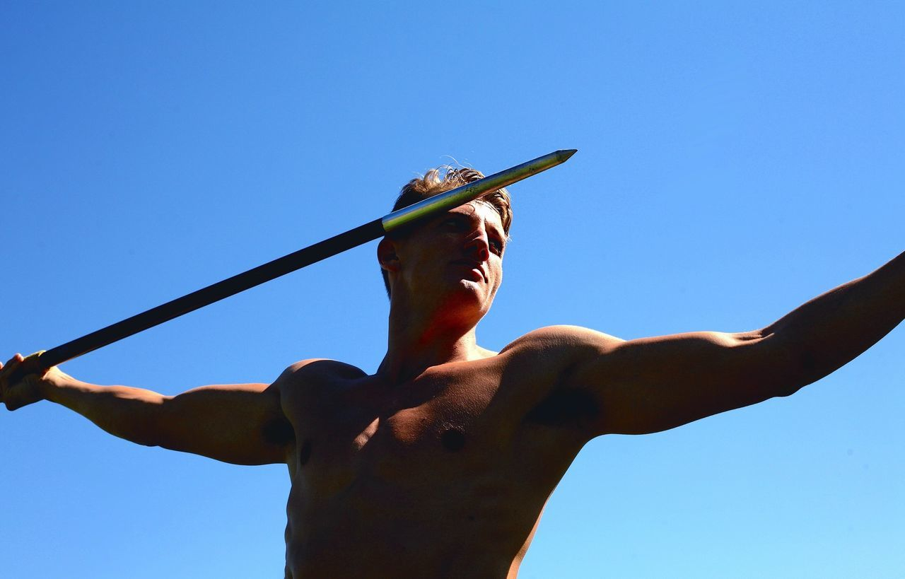 Low angle view of young shirtless man throwing javelin against clear sky