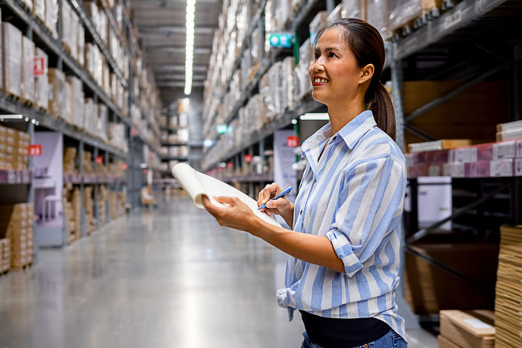Woman writing while standing in warehouse