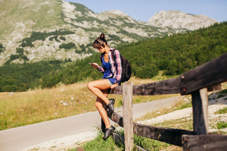 woman travel with smartphone in mountains. backpacking woman chatting on smartphone communication. EyeEm Best Shots Hiking Sky And Clouds Travel Adventure Backpack Beauty In Nature Casual Clothing Communication Female Landscape Leisure Activity Lifestyles Montenegro Mountain Mountain Range Nature Outdoors Picturesque Relaxation Scenics Sexygirl Sky Smart Phone Summer