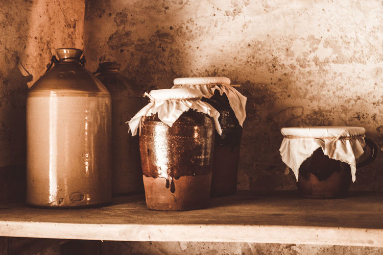 Close-up of jar on table against wall