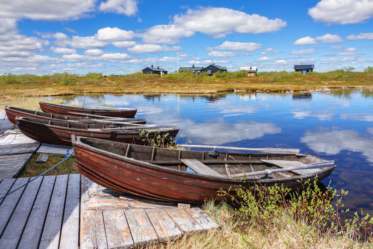 Panoramic view of boats moored on shore against sky