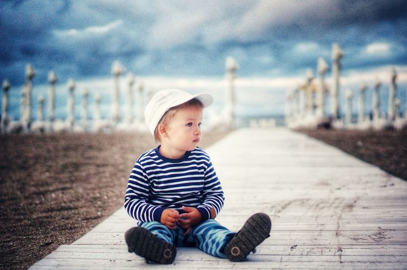 Boy looking down while sitting outdoors