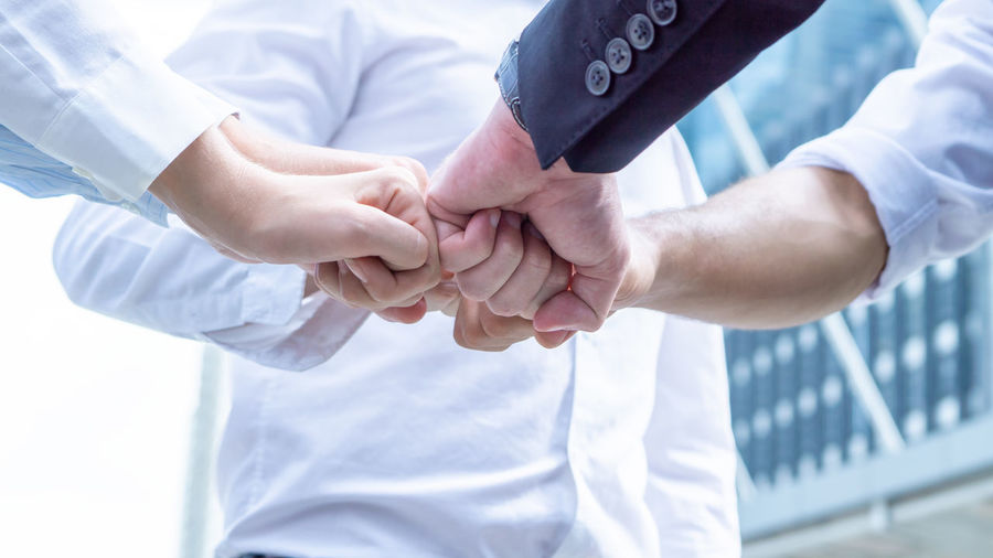 Low angle view of business people fist bumping against modern building