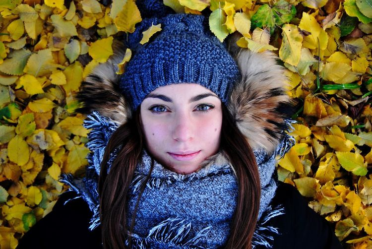 Directly above portrait of beautiful woman lying amidst autumn leaves on field