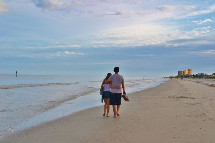 Full length rear view of couple walking at beach with arm around