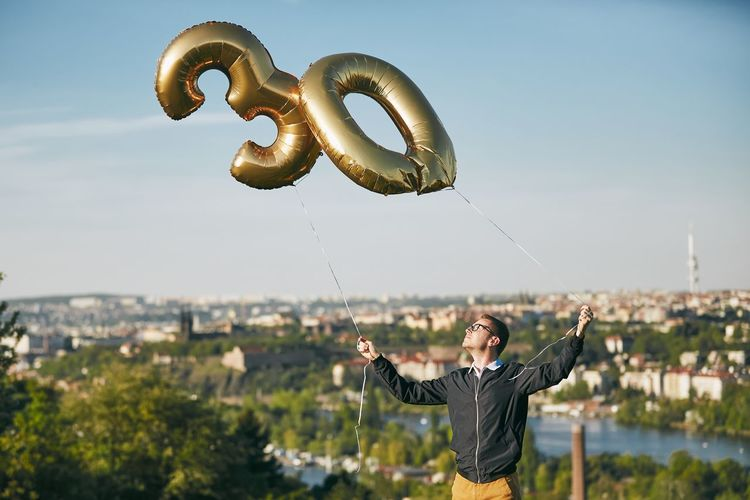 Man holding number 30 helium balloons against cityscape