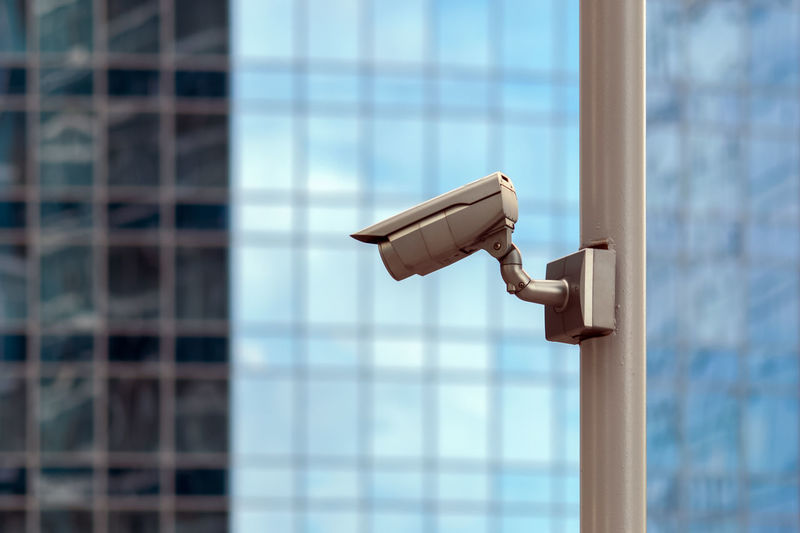 Security camera against glass building wall