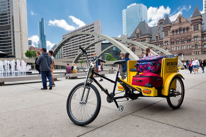 TORONTO, CANADA - JUNE 09, 2018: A cargo bike or rickshaw with some baggages at the Nathan Phillips Square in the city Toronto Architecture Bicycle Building Building Exterior Built Structure Canada City City Life Day Group Of People Incidental People Land Vehicle Men Mode Of Transportation Nathan Phillips Square Nature Office Building Exterior Outdoors People Real People Sky Skyscraper Transportation Travel