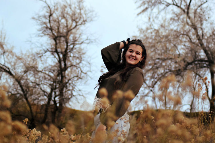 Cheerful Young Woman Posing On Field During Autumn