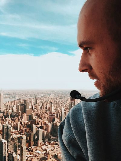 Young man with microphone overlooking cityscape against sky