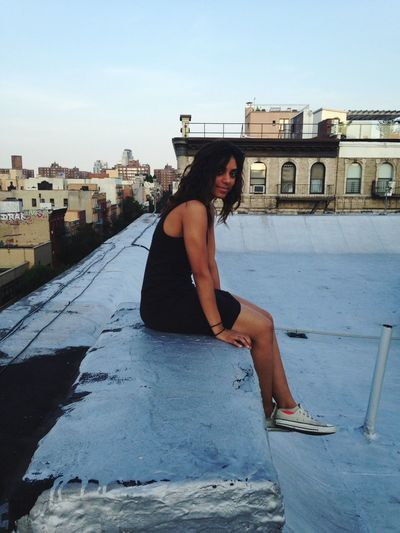 Portrait of woman sitting on retaining wall against sky