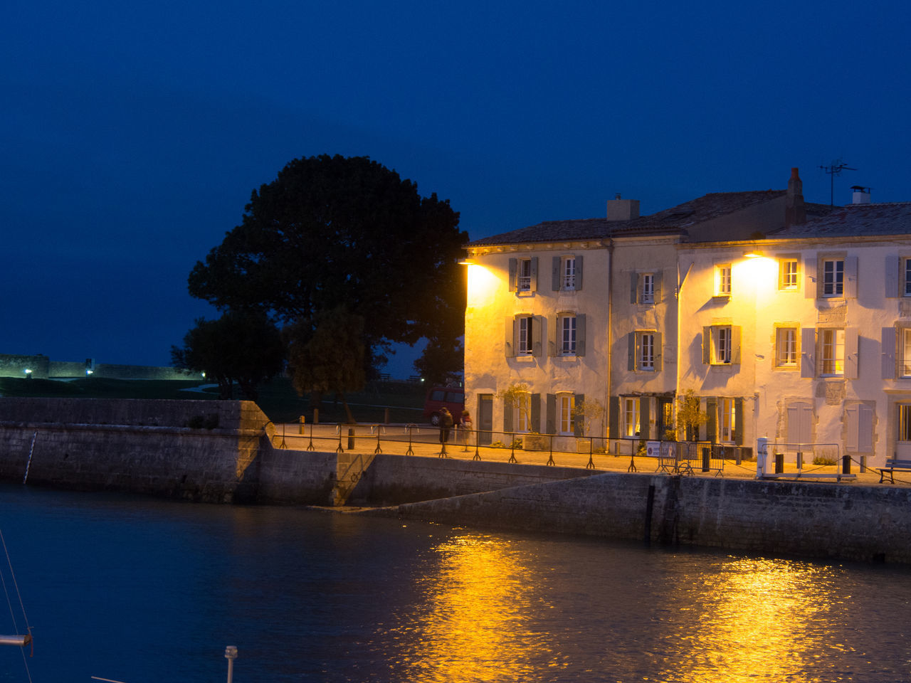 ILLUMINATED BUILDING BY RIVER AGAINST SKY AT NIGHT
