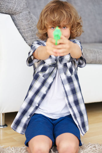 Portrait of boy aiming with toy gun at home