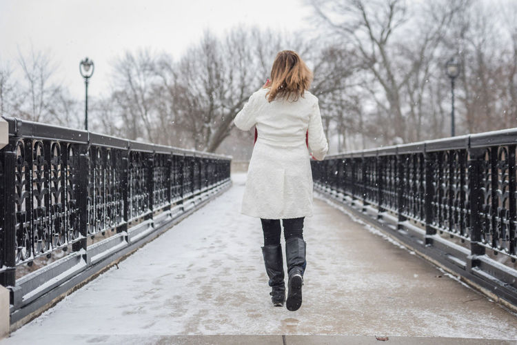 Rear view of woman walking on snow covered bridge against bare trees