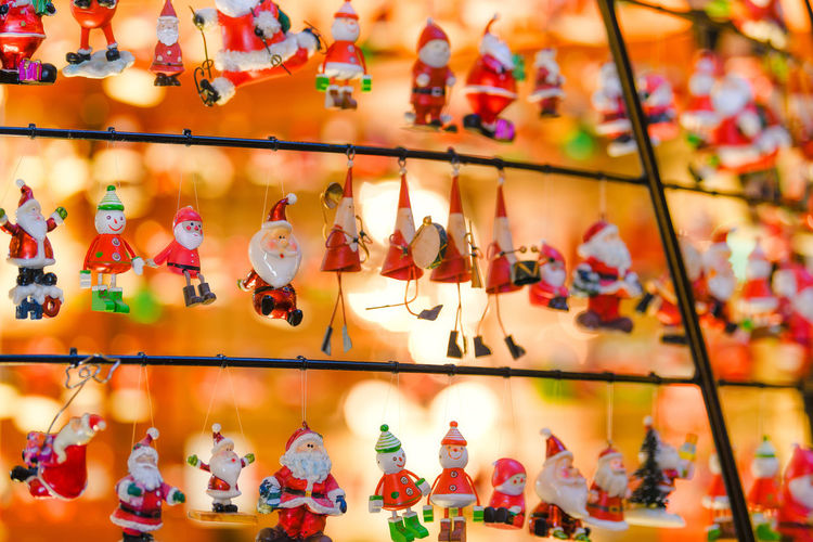 Full Frame Shot Of Christmas Figurines Hanging On Metal In Store